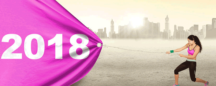 athletic lady pulling a pink banner dated 2018 across a city skyline