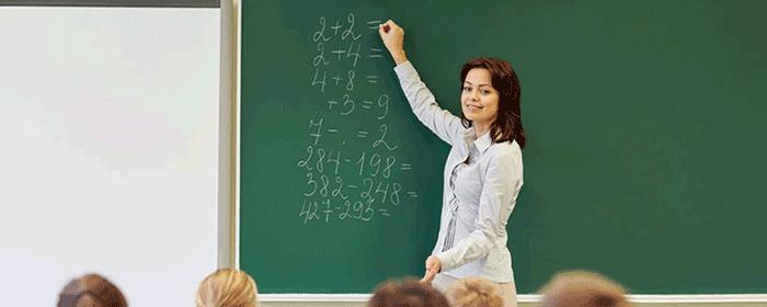 teacher writing in chalk on board