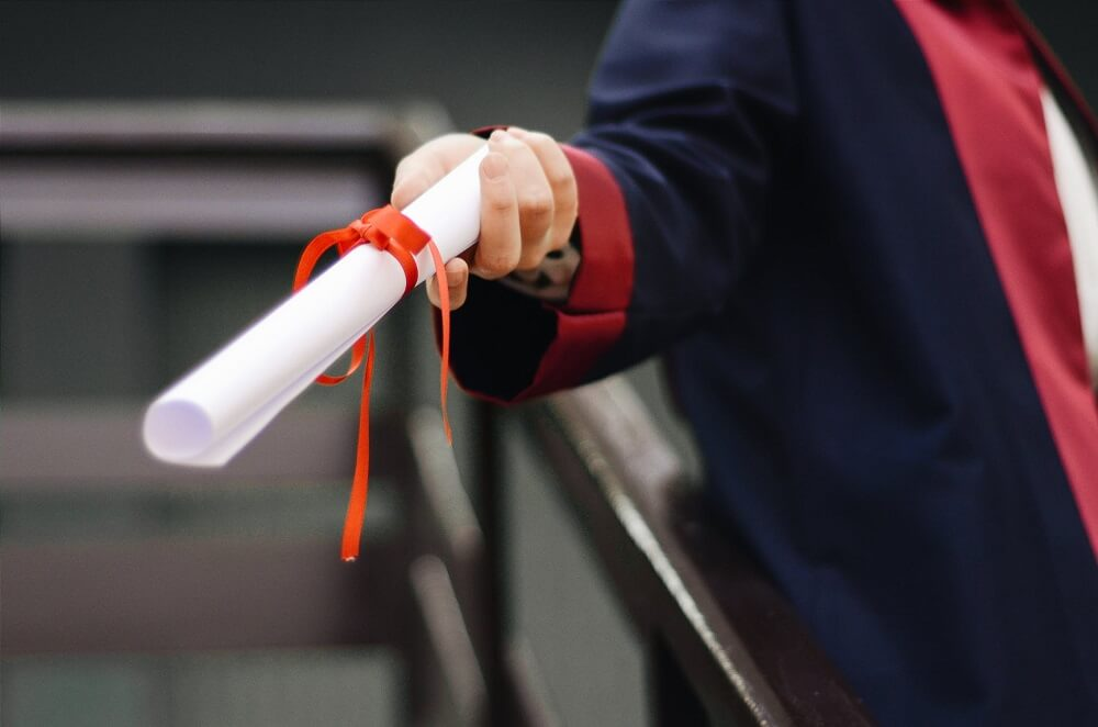 university student holding degree scroll
